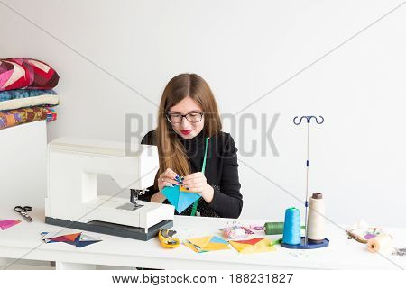 needlework and quilting in the workshop of a young woman - a tailor woman at a desk and sewing machine stitches with hand flaps of colored tissue lying next to the threads, fabrics, needles, pins