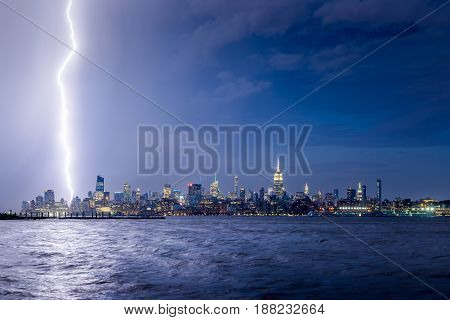 Lightning striking Midtown New York City skyscrapers at night. Stormy skies over Manhattan from the Hudson River