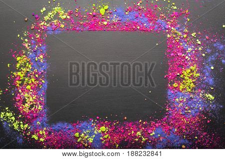 Colorful make-up shadows powder crumbled on black background with copy space. Makeup frame as template