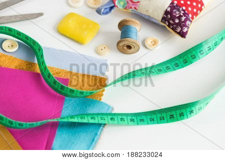 sewing, patchwork, tailoring and fashion concept - close-up on tools of a fashion designer at white table, thread spool, buttons, meter, pincushion, scissors, pieces of colored patchwork fabric, soap