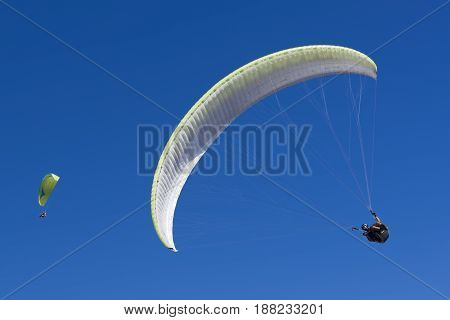 Couple of two paragliding athletes in the blue sky.