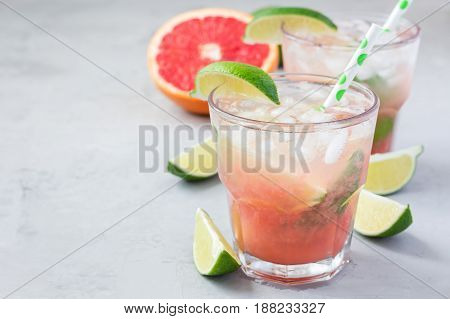 Cold pink cocktail with fresh grapefruit lime and ice cubes on concrete background paloma copy space