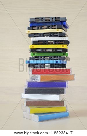 Stack of old colorful dirty audio cassettes and cases on the brown wooden shelf