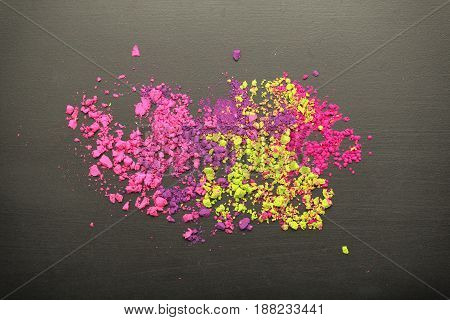 Top view of colorful make-up powder on black chalkboard texture. Flat lay.
