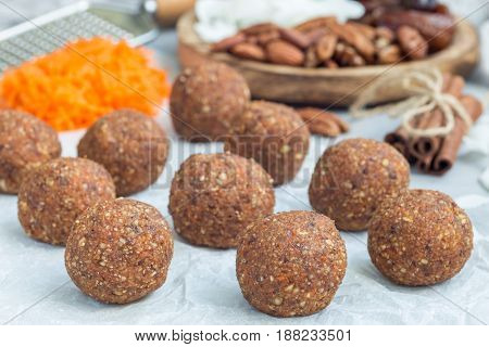 Healthy homemade paleo energy balls with carrot nuts dates and coconut flakes on parchment horizontal