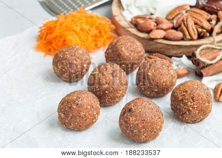 Healthy homemade paleo energy balls with carrot nuts dates and coconut flakes on parchment horizontal copy space