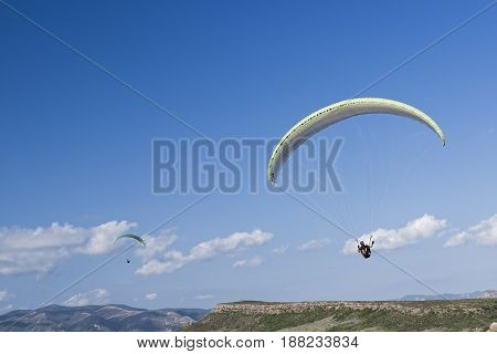 Colorful hang glider in sky over blue. Sardinia sout west coast
