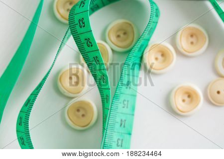 needlework, craft, sewing and tailoring concept - macro with white clothing buttons, cute green measuring meter on white background, top view, flat lay