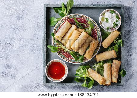 Fried spring rolls with red and white sauces, served in china plate on square wood tray with fresh green salad over gray blue texture background. Flat lay, space. Asian food