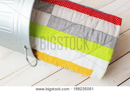 patchwork and fashion concept - close-up on beautiful quilt in a metal bucket on a whitewashed wooden floor, close-up on patchwork products on a light background, top view