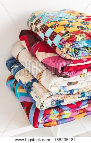patchwork, quilting and fashion concept - close-up on beautiful colorful blankets folded and stored in several rows in height for storage, sale of stitched textile products on white background