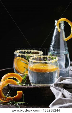 Tonic water cocktail with rosemary and orange. Two glasses and bottle with zest sugar and bubbles in terracotta tray over black texture background. Refreshing beverage alco non alcohol
