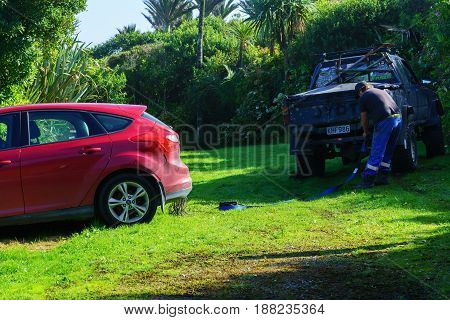 PUNAKAIKI NEW ZEALAND - APRIL 19 2017 : Roadside assistance tries to get the red car out of the mud