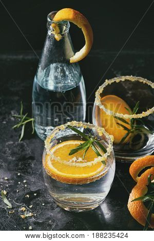 Tonic water cocktail with rosemary and orange. Two glasses and bottle with zest sugar and bubbles over black texture background. Refreshing beverage alco non alcohol