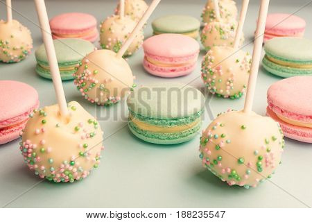 Closeup of colorful macaroons mixed with cake pops on sticks