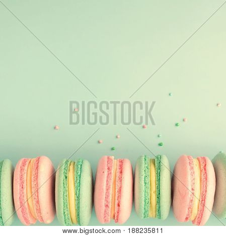Colorful macaroons on blue background with copy space. Flat lay. View from above