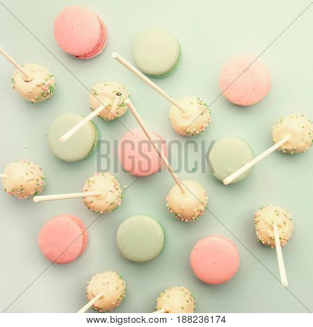 Colorful macaroons mixed with cake pops on sticks. Flat lay. Top view