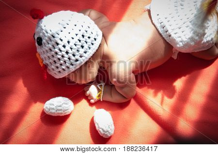 Focus at Asian newborn baby girl with costumes Chicken with two eggs beside the window with sunlight