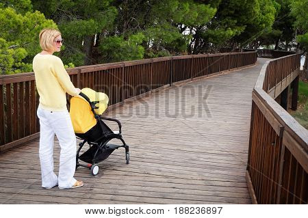 Young mother enjoying walking with stroller outdoors in park