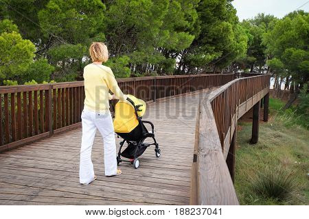 Blond hair woman strolling a baby in carriage outdoors in park