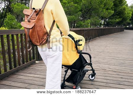 Closeup of young mother strolling a baby carriage on wooden pathway in a park. Back view