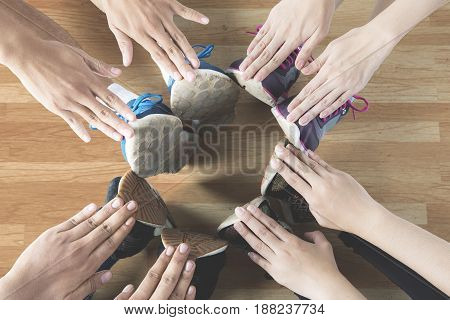 Top view of athletes make a circle with their hands and feet while wearing sports shoes on the wooden floor