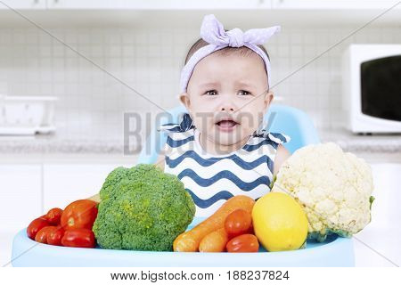 Portrait of a female baby crying alone on a high chair with vegetables in the kitchen. Concept of dislike vegetables
