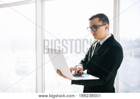 Handsome Business Man In Suit And Eyesglasses With Laptop Against Panoramic Windows Room.
