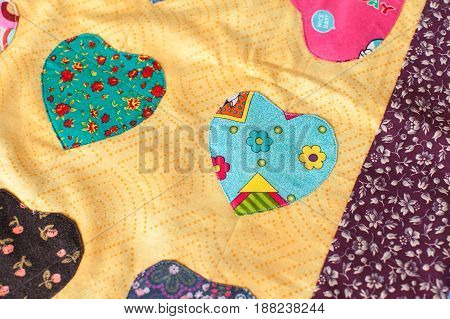 Patchwork quilt with heart print. Part of patchwork quilt as background. Handmade.