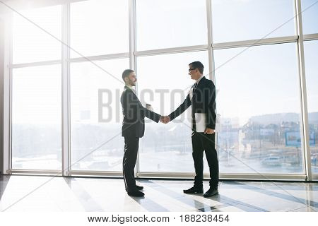 Two Businessmen Greeting With Handshake In Office With Panoramic Windows