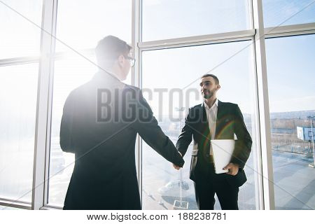 Two Businessmen Greeting In Sunny Office Room Against Windows