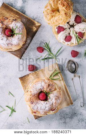 Homemade choux pastry cake Paris Brest with raspberries, almond, sugar powder and rosemary, served on wooden serving board over gray blue texture background. French dessert. Top view