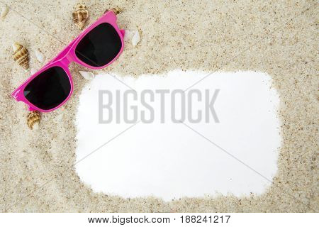 Top view of empty frame with white beach sand seashells and a pink color sun glasses. Vacation concept