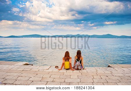 Two Young Girls With Backpacks Sitting Closely