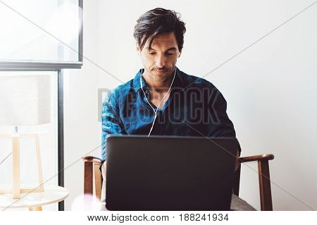 Attractive adult man making video conversation with friends.Man using contemporary notebook on headphones while sitting in vintage chair.Blurred background. Horizontal