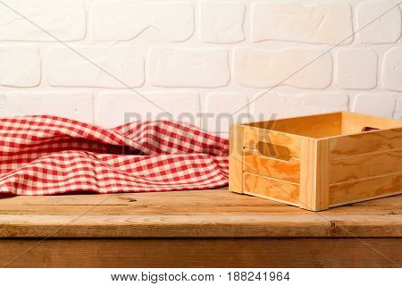 Empty wooden deck table with box and tablecloth over brick wall background