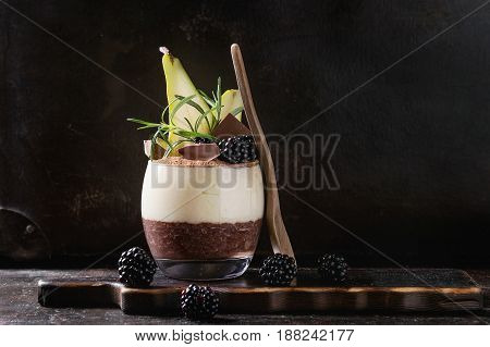Dessert breakfast layered chia seeds, chocolate pudding, rice porridge in glass decorated by fresh blackberries, pear, cocoa powder. Stand with spoon on serving board over dark texture background.