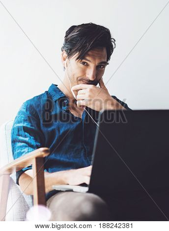 Smiling adult businessman working at office.Man using contemporary notebook on headphones while sitting in vintage chair.Blurred background. Vertical
