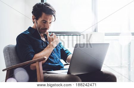 Businessman working at sunny work place.Man using contemporary laptop and headphones while sitting in vintage chair.Horizontal, blurred background