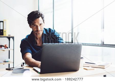 Smiling businessman working on mobile computer at sunny office.Coworker typing on notebook keyboard.Horizontal, blurred background