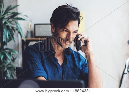 Portrait of Smiling Hispanic businessman working contemporary mobile computer while sitting at the wooden table at sunny office.Man using his mobile phone.Blurred background. Horizontal, flares