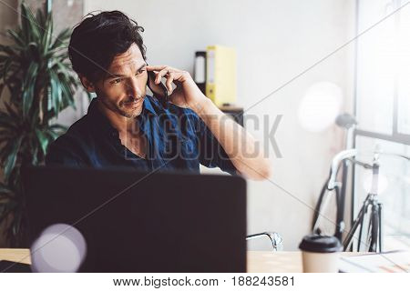 Handsome young businessman working at sunny work place on laptop.Smiling Man making mobile phone conversation while sitting at the wooden table.Blurred background.Horizontal