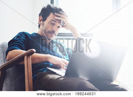 Young man working at home.Man using contemporary laptop and headphones while sitting in vintage chair.Blurred background. Horizontal.Flares effect