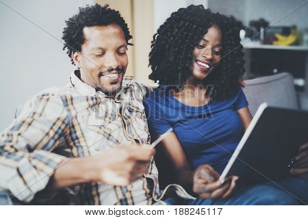 African couple having rest at a home: black girl sitting on sofa, holding touch tablet and laughing, looking through travel photos together with her husband who is sitting close to her