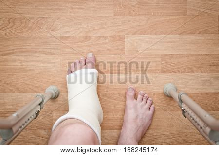 Leg in plaster and crutches on a wooden background