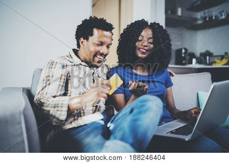 Smiling young african american couple shopping online through modern laptop using credit card at home. Horizontal, blurred background