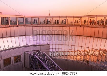 Osaka, Japan - April 28, 2017: Unidentified people on Floating Garden Observatory, Kita-ku district at twilight. A circular rooftop observation deck connecting the twin towers of Umeda Sky Building.