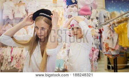 A young mother with a young daughter trying on cute hats in front of a mirror in a clothing store for children