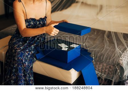 The girl unpacks the blue box with gifts.