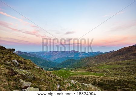 Last Warm Sunlight On Alpine Valley With Glowing Mountain Peaks And Scenic Clouds. Italian French Al
